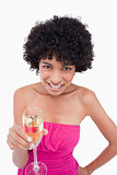 Young woman showing a beaming smile while holding a glass of cha