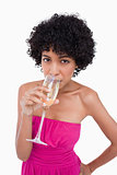 Young woman drinking a glass of champagne against a white backgr