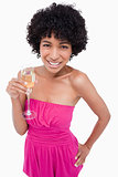Young woman holding a glass of champagne with her hand on her hi