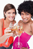 Glasses of white wine being happily clinked by two young females