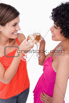 Two young women standing face to face while clinking their glass