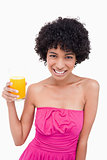 Young smiling woman holding a glass of orange juice