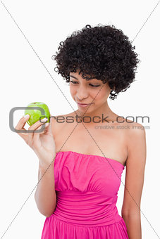 Young woman looking at her delicious green apple