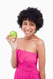Young woman beaming while holding a beautiful green apple