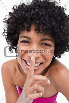 Young woman asking for silence while laughing