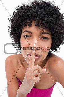 Beautiful teenage placing her finger in front of her mouth to as