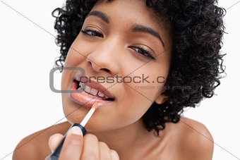 Young woman applying lipstick in a concentrated way