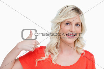 Smiling young blonde woman putting her thumbs up in agreement