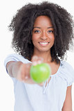 Smiling young woman holding a delicious green apple
