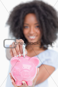 Young woman inserting notes in a piggy bank