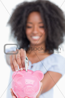 Piggy bank getting dollar notes while held by a young woman