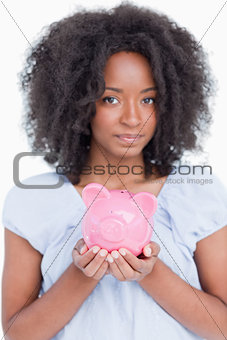 Young woman holding a pink piggy bank close