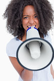Young woman speaking loud into a megaphone
