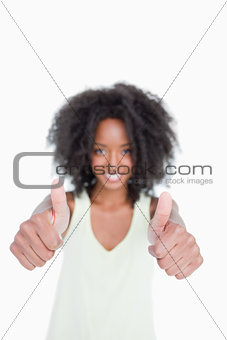 Thumbs up showed by a young woman with curly hair