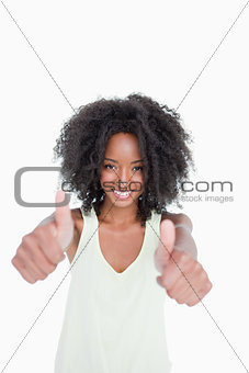 Relaxed young woman putting her thumbs up in satisfaction