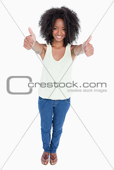 Young relaxed woman standing upright with her thumbs up
