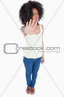 Young woman standing upright while making the hand stop sign