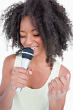 Young woman singing karaoke with a microphone