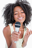 Concentrated young woman singing into a microphone