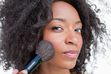 Young serious woman applying blush with powder brush