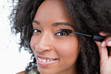 Young smiling woman applying mascara on her eyelashes
