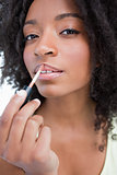 Young woman applying gloss in a concentrated way
