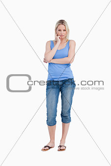 Serious blonde woman standing up with finger on her cheek