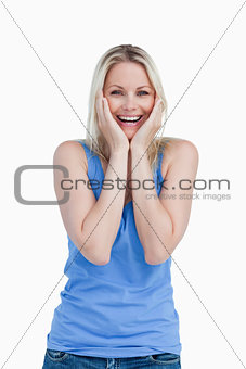 Happy blonde woman showing her surprise by placing her hands on