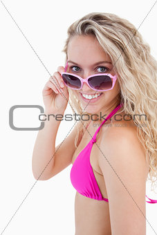 Smiling attractive teenager looking over her sunglasses