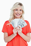 Young attractive woman holding dollar notes in a fan shape