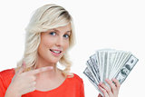Smiling woman pointing at her dollar notes with her finger