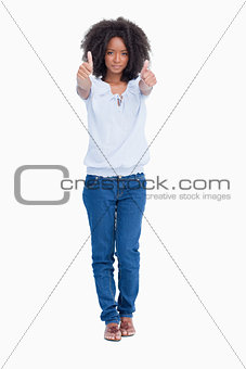 Young serious woman placing her two thumbs up in front of her