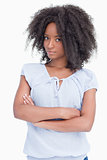 Serious young woman with curly hairstyle crossing her arms