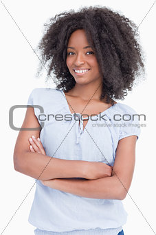 Smiling young curly woman crossing her arms