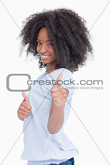Side view of a smiling woman showing her thumbs up
