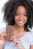 Smiling young woman with curly hair holding a chocolate bar