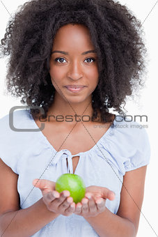 Young curly woman holding a green apple in her hands