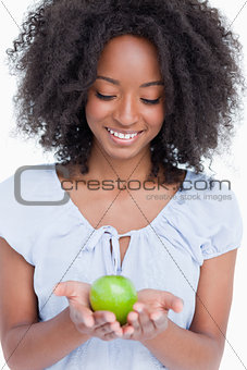 Young woman looking at the green apple held by her