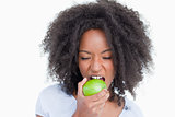 Young woman closing her eyes while eating a green apple