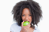 Young woman looking at the camera and eating a green apple