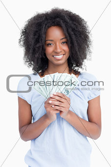 Young smiling woman with curly hair holding a fan of dollar note