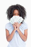 Young curly woman hiding her face behind a fan of dollars