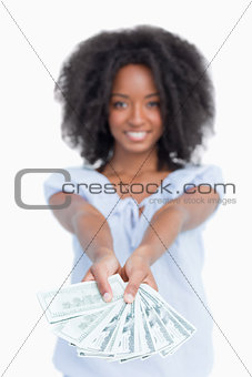 A fan of dollar notes held by a smiling woman with curly hair