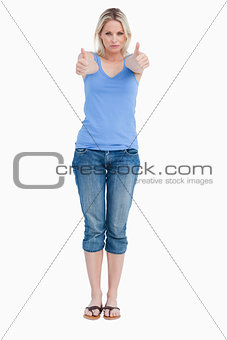 Serious blonde woman showing her thumbs up