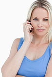 Blonde woman looking at the camera while talking on the phone