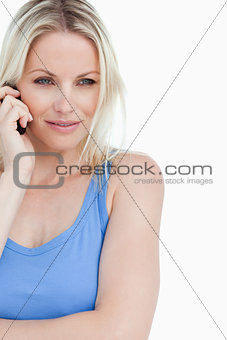 Serious blonde woman standing up while calling