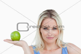 Blonde woman holding an apple in her hand palm