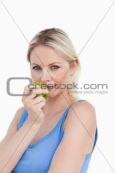 Blonde woman holding a green apple close to her mouth
