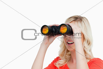 Smiling attractive woman looking with binoculars