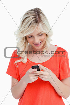 Smiling woman sending a text with her mobile phone